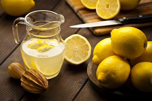 lemons with pitcher of lemonade